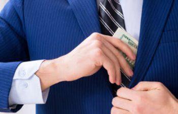 man putting money under his jacket