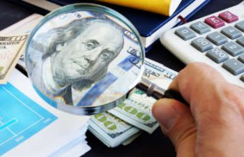 a person using a magnifying to check a banknote