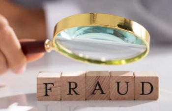 Investigator looking through a magnifying glass at wooden blocks with letters that read FRAUD
