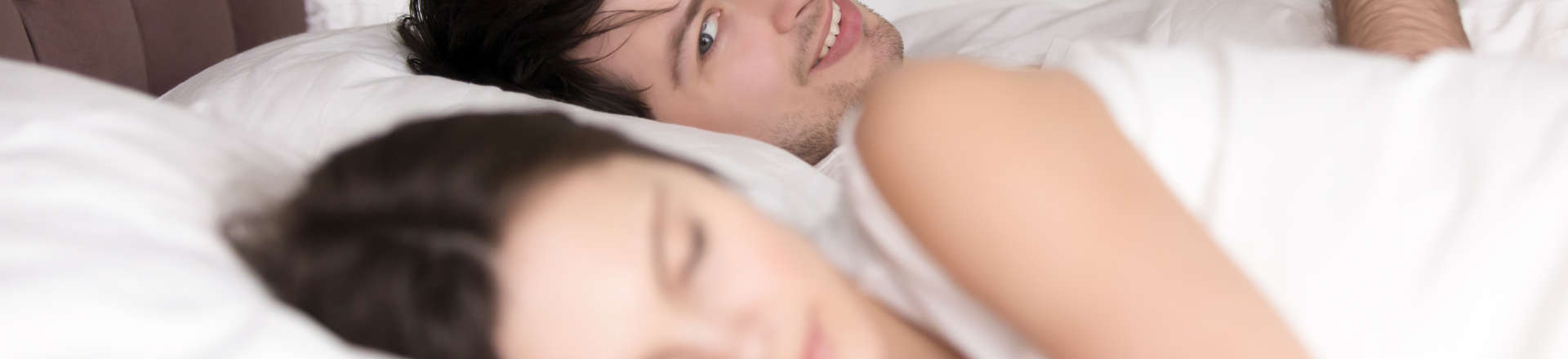 cheerful man in bed texting his lover and glancing at a sleeping by his side woman